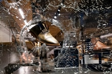 In this Monday, June 1, 2020, photo, shoes are seen through a hole in the damaged glass in the Chelsea neighborhood of…