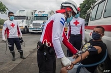 International Red Cross workers check truck drivers pressure and temperature during a blockade at Penas Blancas border between…