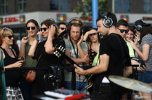 """People with headphones on listen to the music band """"von Welt"""" during a """"Silent Concert"""" at the East Side Gallery in Berlin,…"""