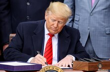U.S. President Donald Trump checks a pen during a signs the United States-Mexico-Canada Trade Agreement (USMCA) during a…