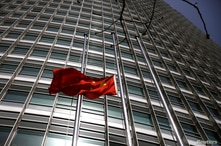 The Chinese national flag flies at half-mast outside a bank in Beijing, as China holds a national mourning for those who died…