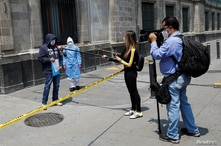 Journalists interview a man, who says he is infected with the coronavirus disease (COVID-19), while he holds a protest outside…