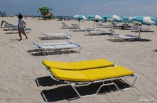 Loungers in pairs, separated to social distancing, are seen as beaches are reopened with restrictions to limit the spread of…