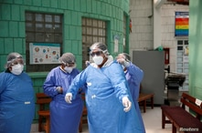 A health worker is helped by a colleague to wearing a protective clothes at the Los Andes Hospital amid the outbreak of…
