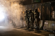Federal law enforcement officers stand guard outside the Mark O. Hatfield U.S. Courthouse after firing tear gas at protesters…