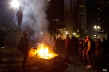 FILE - In this July 4, 2020, file photo, protesters gather near a fire in downtown Portland, Ore. Oregon's largest city is in cr