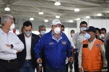 Guatemalan President Alejandro Giammattei (C) wears a face mask as he visits a field hospital set up to treat the new…