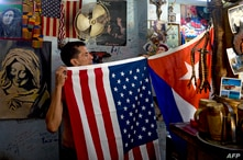 A man shows Cuban and US flags at his house in Havana, on July 29, 2020. - Five years ago, the United States embassy reopened…