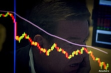 A specialist trader is reflected in a screen at his post on the floor of the New York Stock Exchange, August 21, 2015. The S&P…