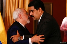 Venezuela's President Nicolas Maduro (R) and Iranian Foreign Minister Mohammad Javad Zarif embrace during their meeting in…