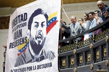 Relatives of political prisoners applaud next to a banner depicting the detained lawmaker Juan Requesens during the swearing-in…