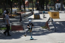 A child plays at a park during an 8 hour permission for children under 14 years old to go outside, as the nation wide…