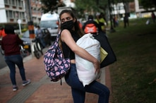 A Venezuelan migrant wearing a face mask holds a bag of food aid donated by officials from the embassy in Bogota of the…