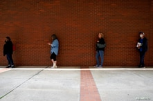 FILE PHOTO: People who lost their jobs wait in line to file for unemployment benefits, following an outbreak of the coronavirus…