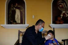 Fray Carlos Caceres gives a beverage to an unaccompanied child who was deported from the U.S., at a shelter in Guatemala City,…