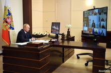 Russian President Vladimir Putin chairs a meeting with members of the government via video link at the Novo-Ogaryovo state…