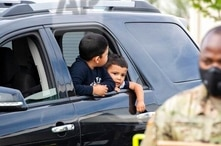 Josue Moreno (R) and his brother, Javier, wait to pick up free food with their family as Washington National Guard soldiers distribute food to residents under state-imposed stay-at-home orders during the novel coronavirus (COVID-19) pandemic in Toppenish, Washington, on Wednesday, April 29, 2020. (Terray Sylvester / VWPics via AP Images)