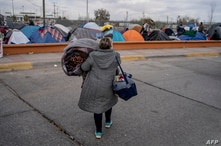 A woman carries belongings to a different part of the campsite near US ports of entry at Chamizal Park on December 19, 2019 in…