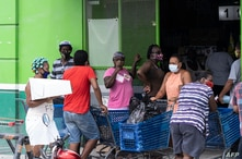 People iqueue outside a supermarket in preparation for hurricane Nana -expected as a Category 1 hurricane with winds up to 74…