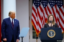 U.S President Donald Trump watches U.S. Court of Appeals for the Seventh Circuit Judge Amy Coney Barrett deliver remarks as he…