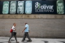 People walks outside the Central Bank of Venezuela (BCV) in Caracas on June 13, 2019. - Venezuela is again issuing new…