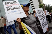 A woman holds placards during a rally to commemorate World Press Freedom Day in Caracas, Venezuela, May 3, 2016. The placards…