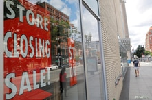 FILE PHOTO: A view shows signs in the windows of Lord & Taylor, advertising a store closing sale, in Boston, Massachusetts, U.S…