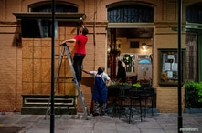 FILE PHOTO: General Manager of Pere Antoine Restaurant Gaige Rodriguez, left, and cook Michael Dillon board up windows as they…