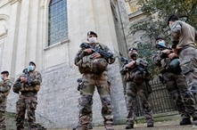 """French soldiers, part of France's national security alert system """"Sentinelle"""", patrol near the Cathedral in Arras as France has raised the security alert for French territory to the highest level after the knife attack in the city of Nice, France."""