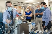 FILE - Astronaut Kate Rubins, center, and support personnel review the Universal Waste Management System, a low-gravity space toilet, in Houston, in this June 18, 2020, photo provided by NASA.