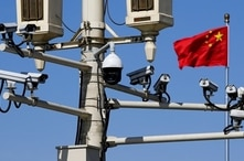 A Chinese national flag flutters near surveillance cameras mounted on a lamp post in Tiananmen Square in Beijing, China, March 15, 2019.
