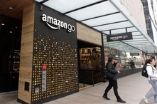 FILE - People walk out of an Amazon Go store in Seattle, Washington, March 4, 2020. Amazon is rolling out the Amazon One, a new device for contactless transactions that scans an individual's palm.