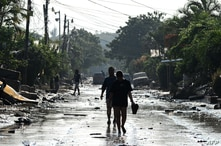 People walk along a street in Planeta, municipality of La Lima, in the Honduran department of Cortes, on November 9, 2020,…