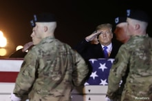 U.S. President Donald Trump salutes a transfer case holding the remains of Chief Warrant Officer David Knadle, who was killed…