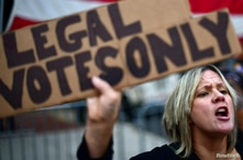 """FILE PHOTO: Carri Dusza, a supporter of President Donald Trump, holds a placard stating """"LEGAL VOTES ONLY"""" while shouting…"""