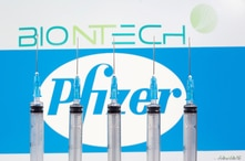 FILE PHOTO: Syringes are seen in front of displayed Biontech and Pfizer logos in this illustration taken November 10, 2020…
