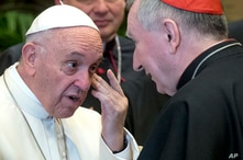 FILE - In this Dec. 21, 2017 file photo, Pope Francis talks to Vatican Secretary of State, Cardinal Pietro Parolin, on the…