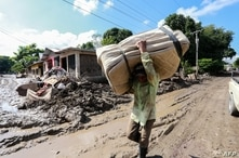 A local resident, victim of tropical storms Eta and Iota, carries a matress along a street covered in mud during a visit of…