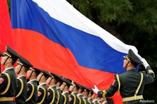 An honour guard holds a Russia flag during preparations for a welcome ceremony for Russian President Vladimir Putin outside the…