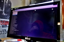 A man is reflected in a monitor as he takes part in a training session at Cybergym, a cyber-warfare training facility backed by…
