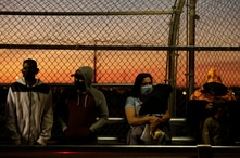 """Migrants in the """"Remain in Mexico"""" program queue at the Paso del Norte border bridge to reschedule their immigration hearings…"""