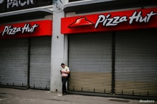 A man looks at his cell phone while a pizza restaurant looks closed after health authorities reverse the measures of reopening…