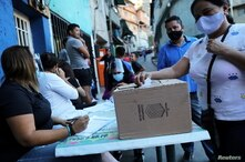 A woman casts her vote during a popular consultation meant to reject December 6 parliamentary election at the low income…
