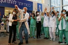 Medical teams celebrate before receiving coronavirus disease (COVID-19) vaccines as Israel kicks off a coronavirus vaccination…