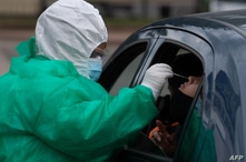 A person undergoes a PCR test for COVID-19 at a testing facility set up in front of the Uruguayan Congress in Montevideo on…
