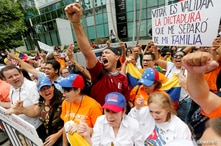 Venezuelans including Marcos Carbono (C) protest the presidential election in Venezuela outside the Venezuelan consulate where…