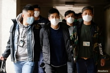 Pro-democracy activist Lester Shum is taken away by police officers after over 50 Hong Kong activists arrested under security…