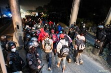Hondurans taking part in a new caravan of migrants, set to head to the United States, walk past a police checkpoint after…