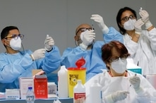 Health workers prepare doses of the Pfizer-BioNTech COVID-19 vaccine at a coronavirus disease (COVID-19) vaccination center in Naples, Italy, Jan. 8, 2021.