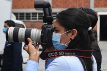 A photojournalist wears a surgical mask during a press conference in San Salvador on April 21, 2020. (Photo by Yuri CORTEZ /…